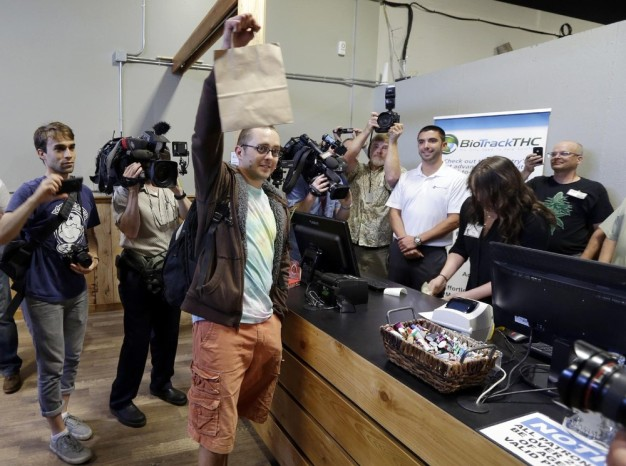 Cale Holdsworth, de Abilene, au Kansas, tient son achat après avoir été le premier en ligne pour acheter de la marijuana récréative légale à Top Shelf cannabis, le mardi 8 Juillet 2014 à Bellingham, Washington Holdsworth avait été en ligne depuis 04h00 du matin. (Photo par Ted S. Warren / AP Photo)