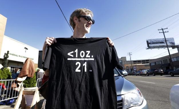 Terry Martin affiche un tee-shirt qu'il vend célébrant la marijuana légale en face de cannabis City, il attend avec d'autres le premier jour que les ventes de weed de loisirs soit légal dans l'état. Mardi, 8 Juillet 2014 à Seattle t-shirt. Les symboles traduisent qu'une once de pot et plus de 21 ans c'est légal. Le magasin est le premier shop à Seattle qui vende légalement. (Photo par Elaine Thompson / AP Photo)